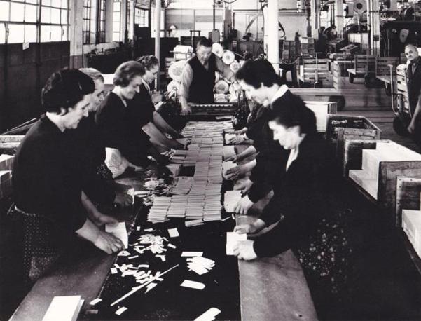 """Primi anni '60. Operaie addette alla cernita e all'impacchettatura dei fiammiferi piatti """"Minerva"""", ottenuti con lo """"sfoliato"""" di tronchi di pioppo. Negli anni '80 furono inventate le macchine """"impaccatrici"""" (Foto: Archivio Tunesi)"""