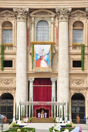 San Pietro: non appena Ratzinger ha concluso la formula di beatificazione, è stato svelato l'arazzo appeso alla loggia centrale della Basilica (Afp)