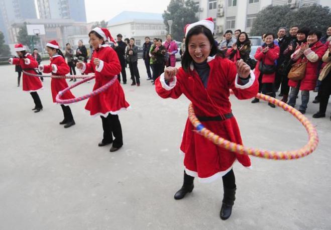 Vestite da Babbo Natale fanno una gara di hula hoop a Hefei Anhui, Cina (Reuters)