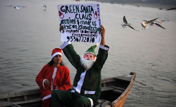 Un Babbo Natale tradizionale e uno in versione «green» ala periferia di Allahabad (Afp)