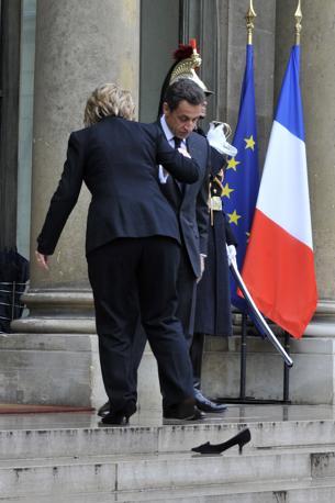 Il segratario di Stato americano, Hillary Clinton, in visita ufficiale dal presidente francese Nicolas Sarkozy, perde la scarpa destra salendo la scalinata dell'Eliseo a Parigi (Philippe Wojazer/Reuters)