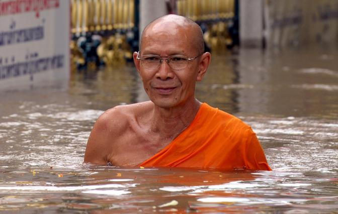 Un monaco buddista attraversa il centro di Ayutthaya, l'antica capitale della Thailandia, completamente allagata (Afp/Kittiwongsakul)