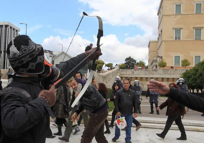 Un manifestante scaglia una freccia contro le forze dell'ordine (Epa/Panagioutou)